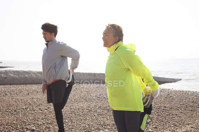 Мужчина и женщина тренируются, стоя на одной ноге на Брайтон Бич — стоковое фото