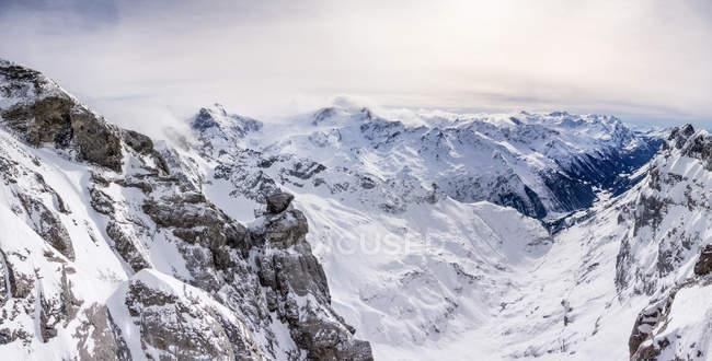 Schneebedeckte Berge mit niedrigen Wolken, Panoramablick — Stockfoto