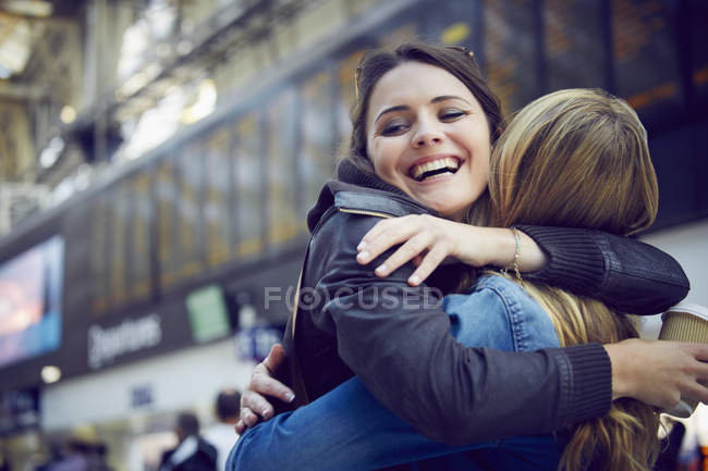 Women hugging in train station concourse, London, UK — Stock Photo