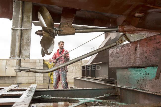 Маляр, использующий мойку под давлением для очистки корпуса и винта корабля — стоковое фото
