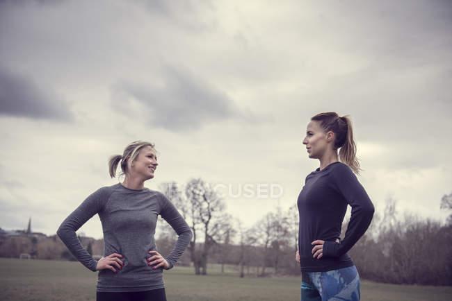 Femmes portant des vêtements de sport dans les mains de champ sur les hanches face à face souriant — Photo de stock