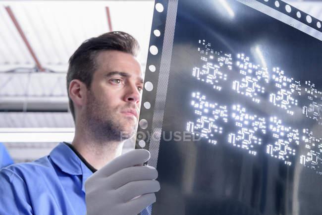 Рабочий осматривает металлический шаблон для печатной платы на монтажном заводе — стоковое фото