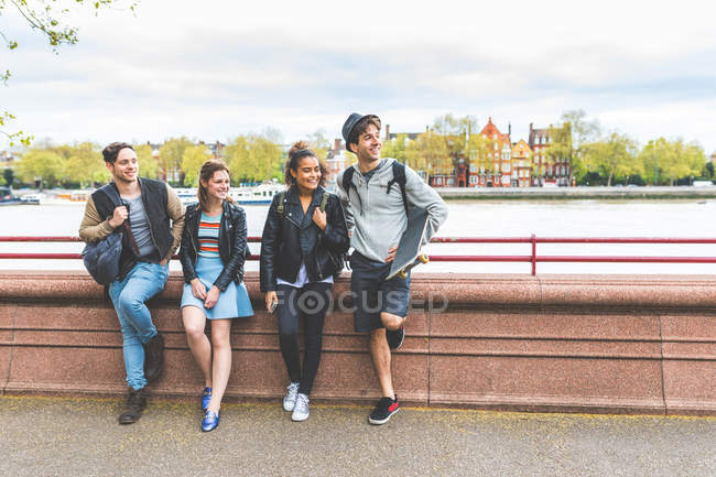 Four young adult friends leaning against lakeside wall in Battersea Park — Stock Photo