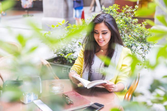 Mujer en la acera mesa de café lectura libro sonriendo - foto de stock