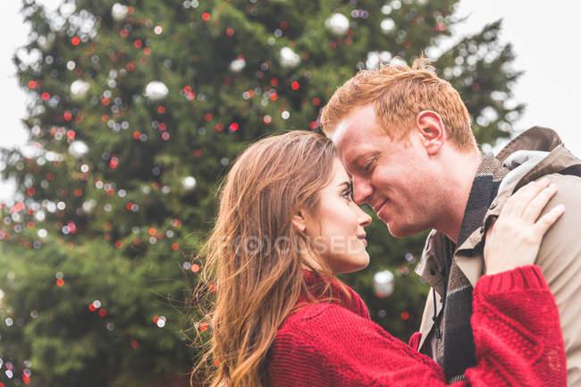 Paar umarmt sich vor dem Weihnachtsbaum — Stockfoto