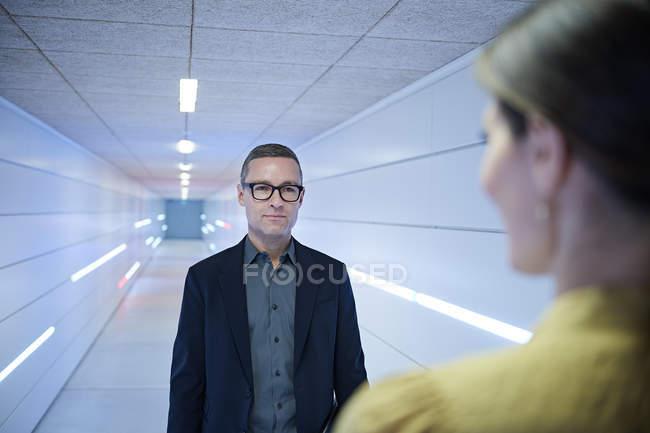 За плече погляд бізнесмен наближається жінка в кабінеті коридору — стокове фото