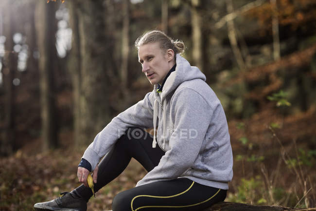 Mid adult man wearing sports clothes holding banana looking away — Stock Photo