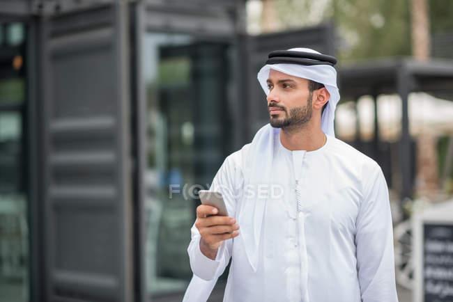 Mann trägt traditionellen orientalischen Kleidung mit Smartphone, Dubai, Vereinigte Arabische Emirate — Stockfoto