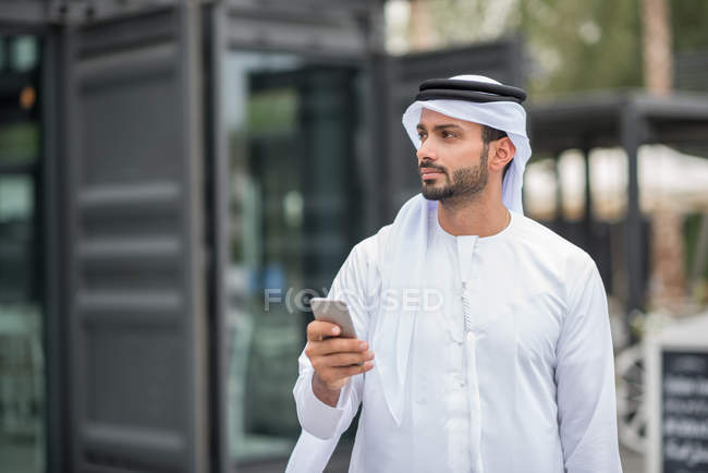 Man wearing traditional middle eastern clothing using smartphone, Dubai, United Arab Emirates — Stock Photo