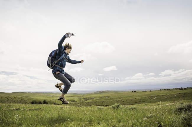 Alpinista de adolescente masculina pulando ar meados na paisagem, Cody, Wyoming, EUA — Fotografia de Stock