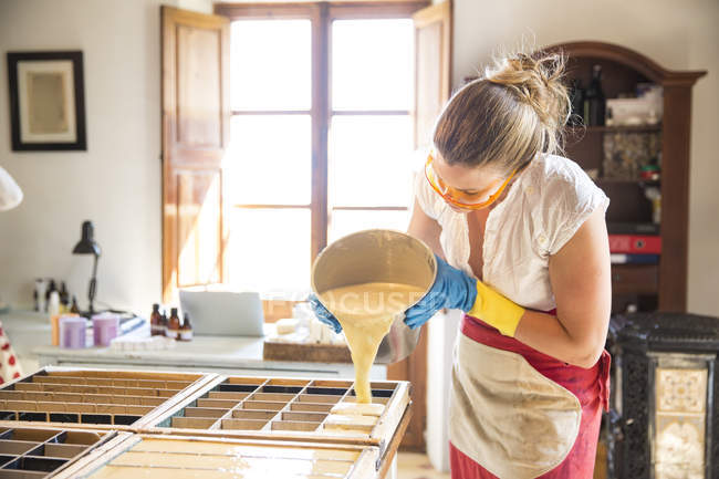 Young woman pouring liquid lavender soap into moulds in handmade soap workshop — Stock Photo
