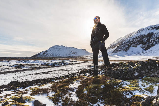 Man standing, looking at view, low angle view, Arnarstapi. Iceland — Stock Photo