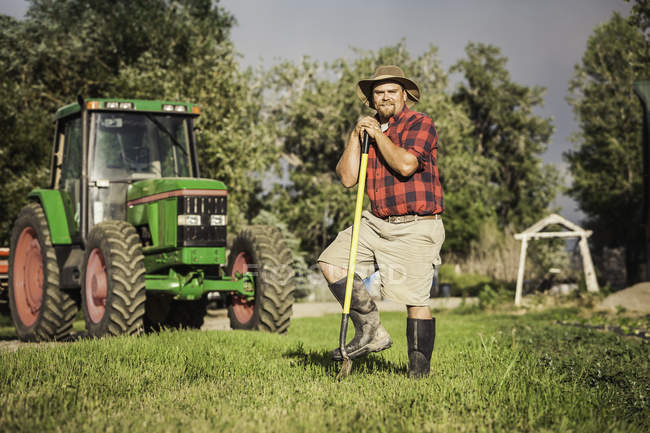 Farmer in front of tractor leaning against hoe looking at camera smiling — Stock Photo
