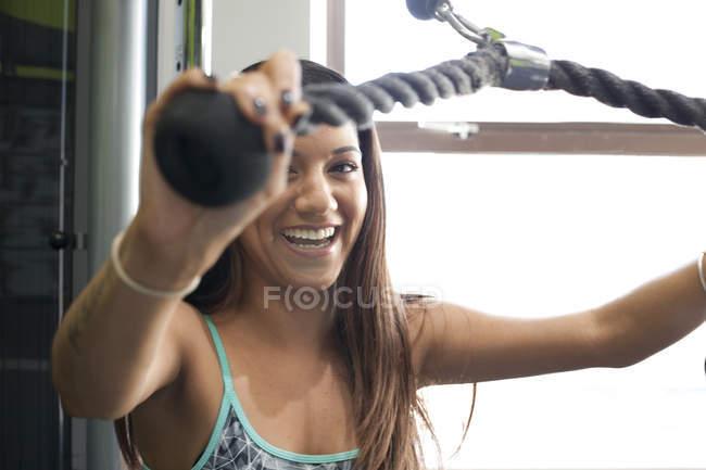 Frau im Fitness-Studio mit Heimtrainer, Blick auf die Kamera zu Lächeln — Stockfoto