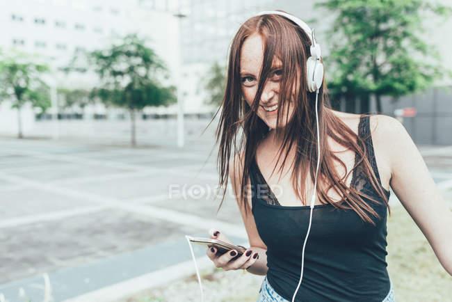 Портрет молодой женщины, слушающей наушники и танцующей снаружи офисного здания — стоковое фото
