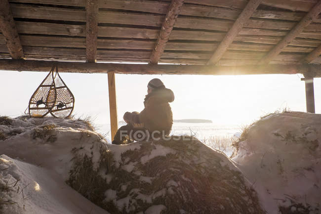 Man sitting on snowy haystack in barn with snow shoes, Ural, Russia — Stock Photo