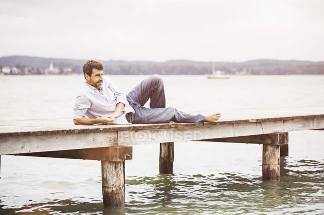 Reifer Mann entspannend auf pier — Stockfoto