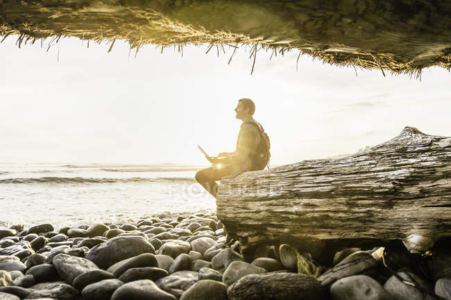 Man sitting with laptop looking out from beach in Juan de Fuca Provincial Park, Vancouver Island, British Columbia, Canada — Stock Photo