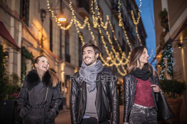Vista frontale a basso angolo di amici che camminano per strada la sera sorridendo — Foto stock