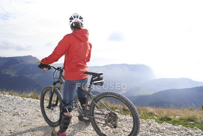 Rear view of cyclist on bicycle looking at view of mountains — Stock Photo