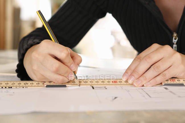 Cropped view of woman drawing blueprint — Stock Photo