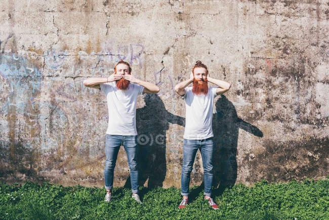 Porträt des jungen männlichen Hipster Zwillinge mit roten Bärte stehen vor der Wand mit Händen, Mund und Ohren abdecken — Stockfoto