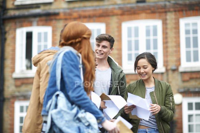 Heureux étudiants de sexe masculin et féminin lisant les résultats des examens sur le campus — Photo de stock