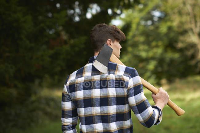 Rückansicht eines Mannes im Wald mit Axt auf der Schulter — Stockfoto