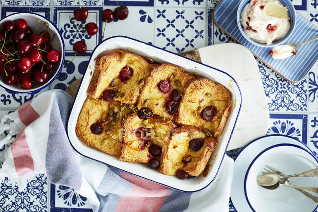 Cherry bread, butter pudding and fresh cherries on table — Stock Photo