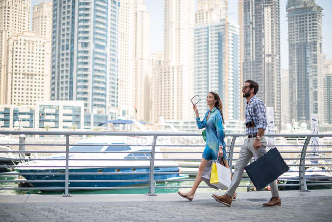 Couple strolling on waterfront carrying shopping bags, Dubai, United Arab Emirates — Stock Photo