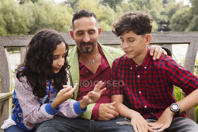 Батько сидить на лавці з сином і дочкою, дочка розраховує на пальці — стокове фото