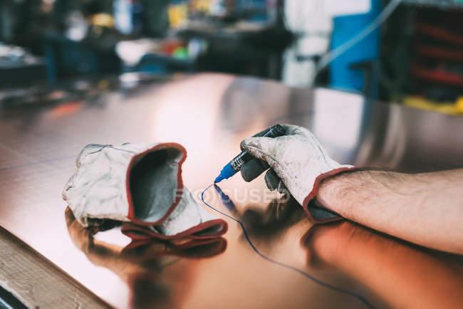 Hände eines Metallarbeiters zeichnen Umrisse, die an der Schmiedewerkbank auf Kupferblech geschnitten werden — Stockfoto