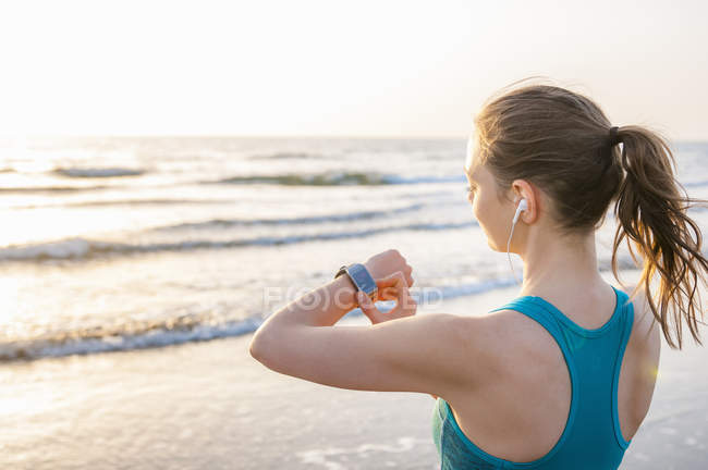 Через плечо зрения середине взрослой женщины океаном носить наушники, глядя на наручные часы — стоковое фото