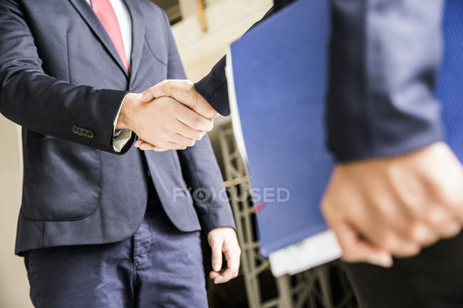 Cropped shot of businessmen shaking hands outside office — Stock Photo