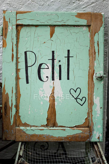 Rustic green vintage door with petit sign — Stock Photo
