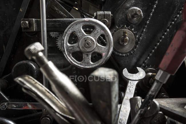 Tools near printing machinery in printing press workshop — Stock Photo