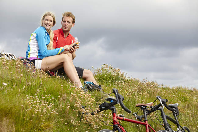 Cyclists relaxing and chatting on grassy hilltop — Stock Photo