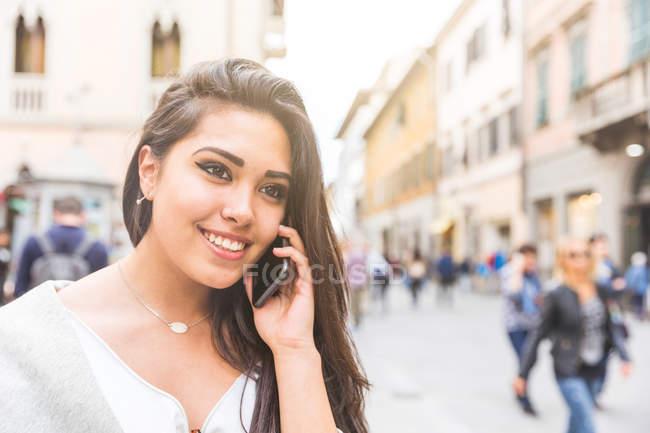 Mulher na rua usando o smartphone sorrindo — Fotografia de Stock