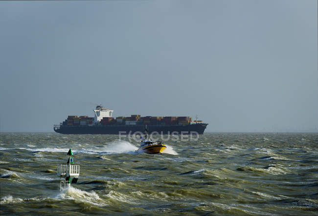 Container ship sailing on Westerschelde river, towards open sea, after visiting Antwerp harbour — Stock Photo