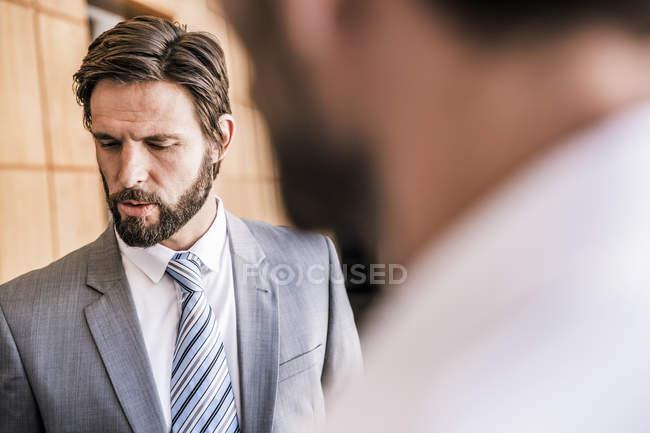 Bärtiger Geschäftsmann blickt nach unten — Stockfoto