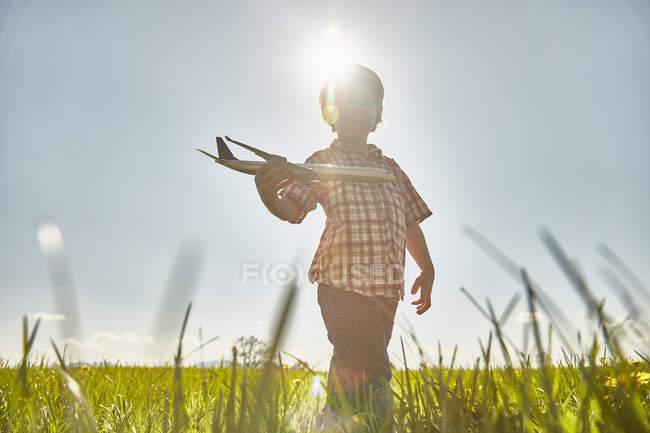 Garçon dans le champ ensoleillé jouer avec jouet avion — Photo de stock