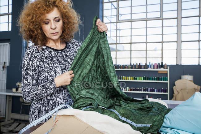 Designer de moda feminino maduro têxteis na mesa de oficina de medição — Fotografia de Stock