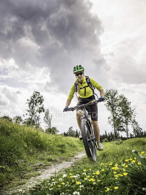 Mujer ciclismo de montaña, Augsburg, Baviera, Alemania - foto de stock
