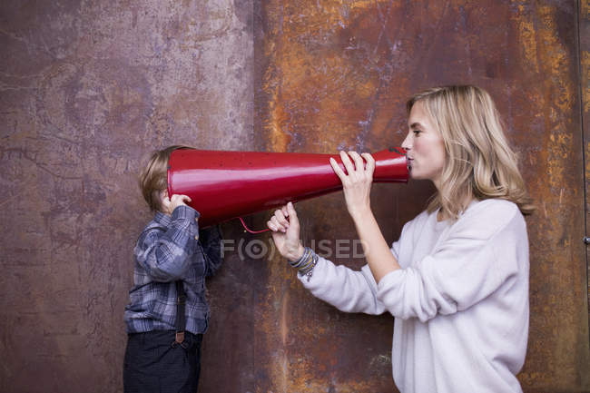 Woman speaking into megaphone, young boy listening, head in megaphone — Stock Photo