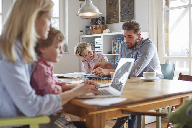 Parents and sons working in home office — Stock Photo