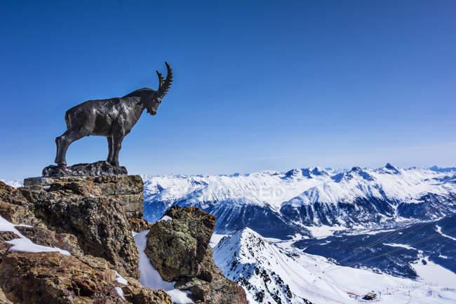 Mountain goat statue on ridge in snow covered mountains, Sankt Moritz, Engadin, Switzerland — Stock Photo