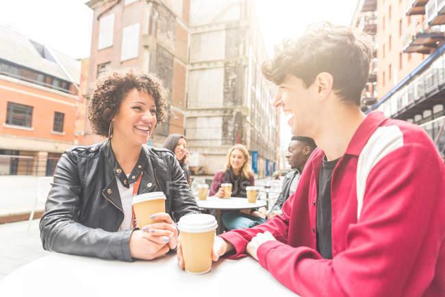 Coppia al caffè marciapiede tenendo tazze usa e getta sorridente — Foto stock