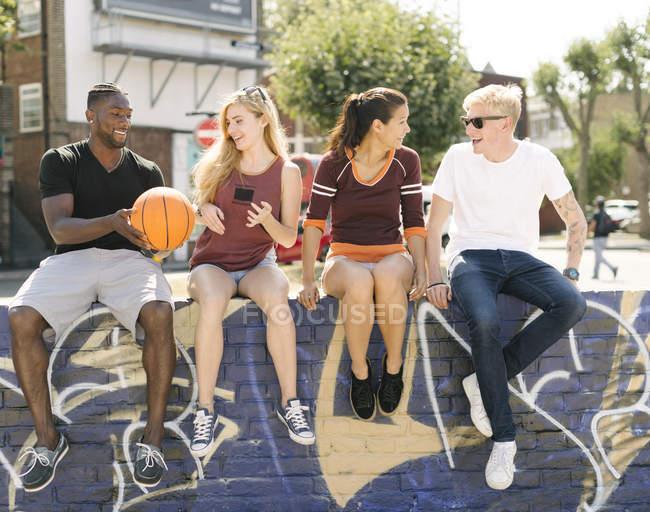 Amis de basket-ball masculin et féminin assis bavardant au skatepark de la ville — Photo de stock