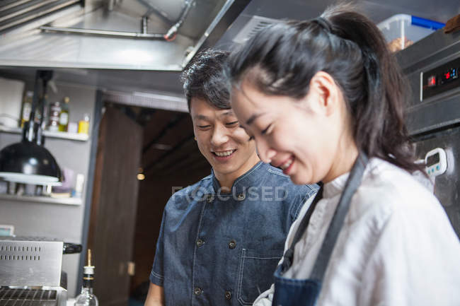 Asian Chefs in commercial kitchen smiling — стокове фото
