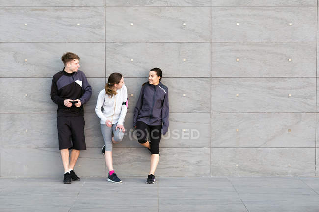 Three friends, wearing sports clothing, leaning against wall, chatting — Stock Photo